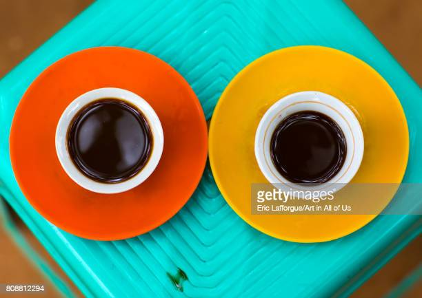 Two cups of coffee seen from above on a green plastic table Omo valley Key Afer Ethiopia on June 8 2017 in Key Afer Ethiopia
