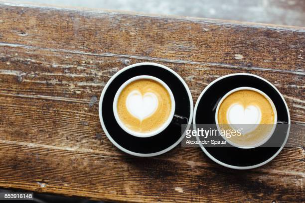 two cups of coffee with foam latte art on a wooden table seen from above - dois objetos - fotografias e filmes do acervo