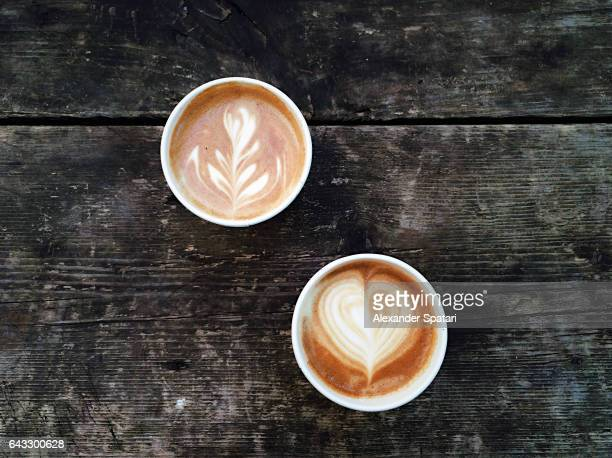 Two cups of coffee with foam latte art seen from above