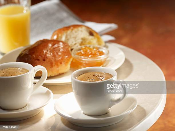 Two cups of espresso with brioche, jam and orange juice