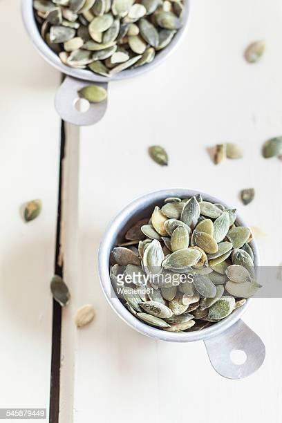 Two cups of pumpkin seeds on white ground