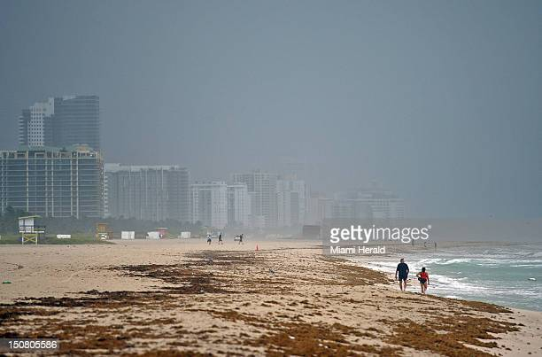 Two curious beachgoers walk their dog on the beach at Miami Beach Florida as Tropical Storm Isaac's outer weather band makes it way to South Florida...
