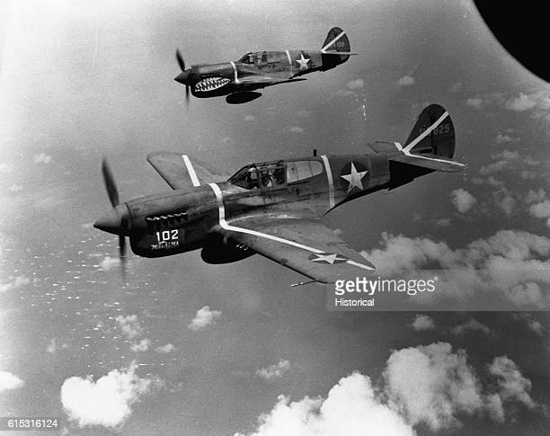 "Two Curtiss P-40 ""Warhawk"" fighter planes in flight. This model was commonly used by United States forces during World War Two."