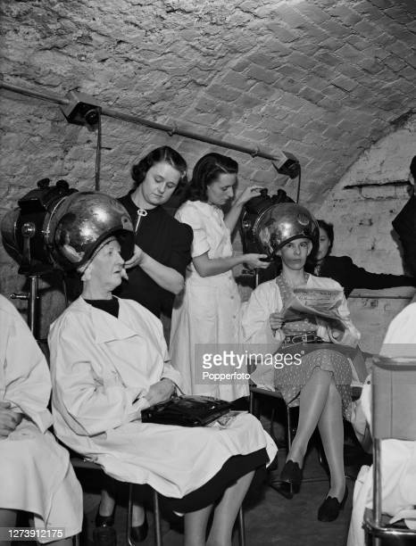 Two customers have their hair washed and set under dryers by assistants in the underground basement bomb shelter of a hair salon in the West End of...