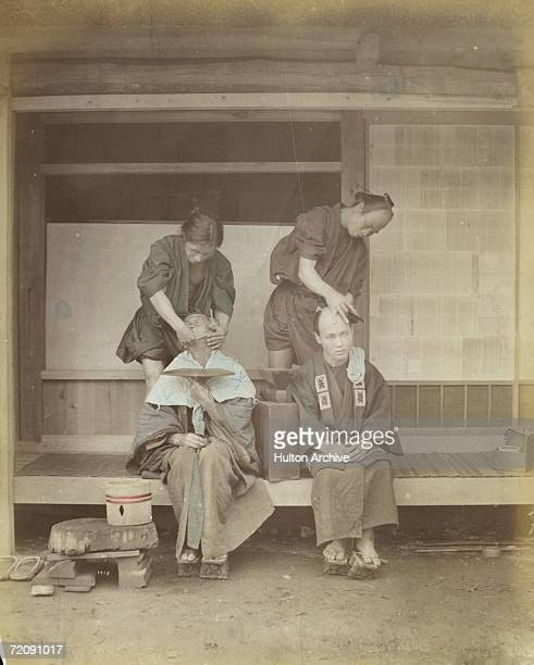 Two customers in traditional Japanese dress are attended by barbers circa 1920