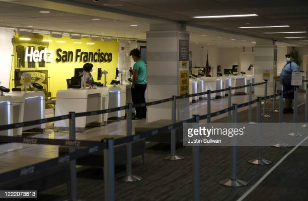 Two customers wait in line to rent a car from Hertz at San Francisco International Airport on April 30 2020 in San Francisco California According to...