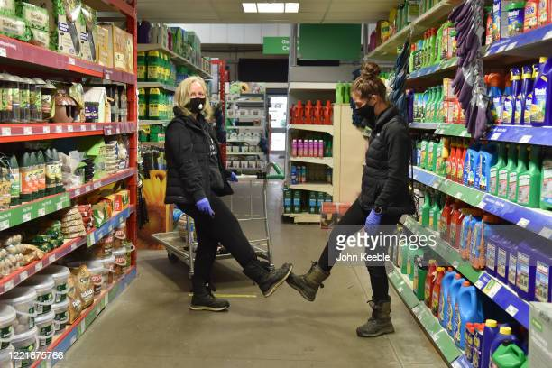 Two customers wearing face masks have a bit of fun by doing a social distancing greeting by touching feet while shopping at the Homebase store in...