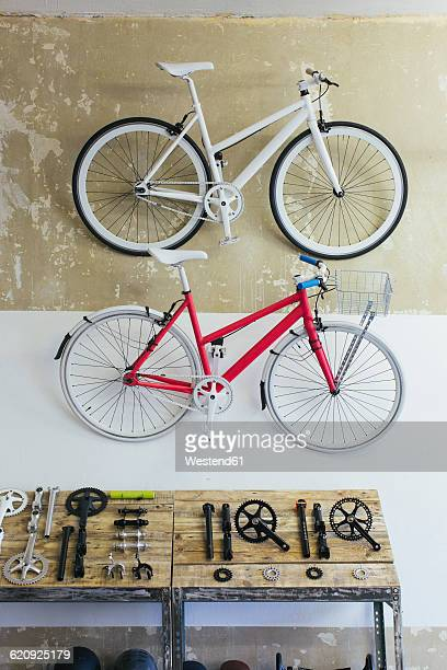 Two custom-made bicycles hanging on the wall in a store