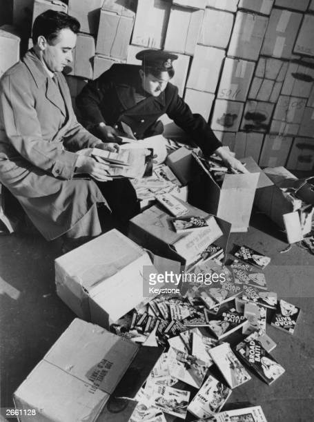 Two customs officers sorting through piles of books condemned as obscene in a shed at London docks