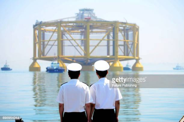 Two customs officials watch a smart deepsea salmon farm being moved onto a semisubmersible transporter in east China's Shandong province for a...