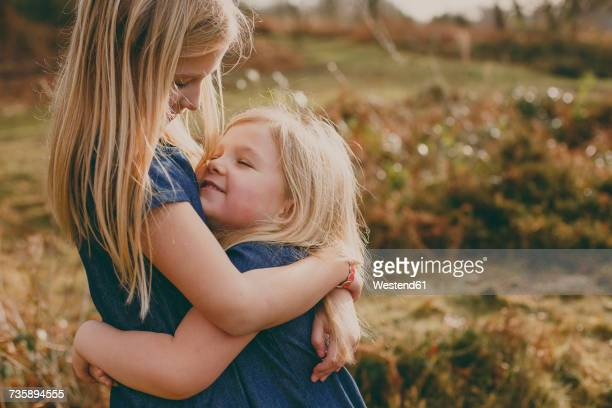 two cute blond sisters cuddling outdoors - sister stock photos and pictures