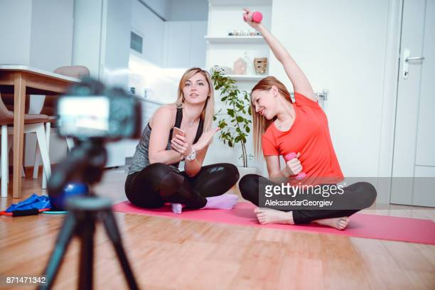 two cute blonde females making vlog about pilates and healthy lifestyle - aleksandar georgiev stock photos and pictures