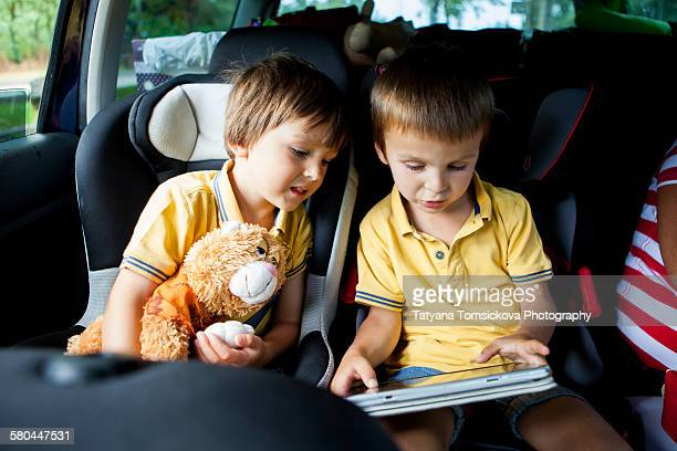 Two cute boys, playing on tablet in the car