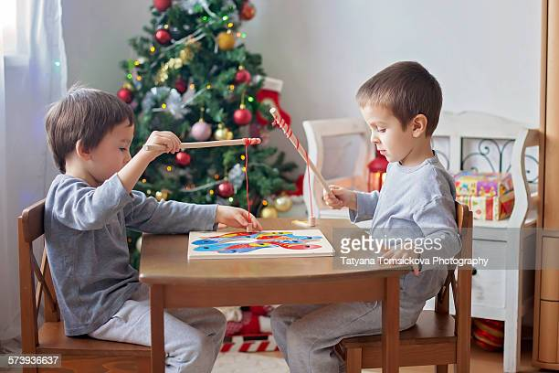 Two cute boys, playing with wooden magnet puzzle
