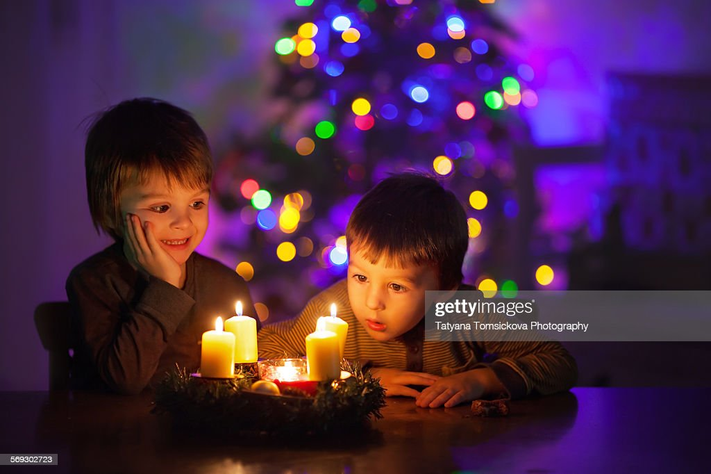 Two cute boys, watching candles burning : Stock Photo