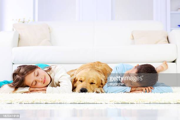 Two cute children and dog sleeping down on white carpet.