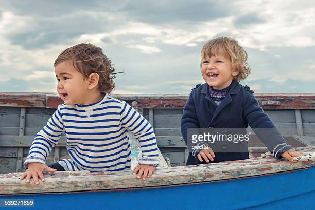 Two cute children playing in the boat