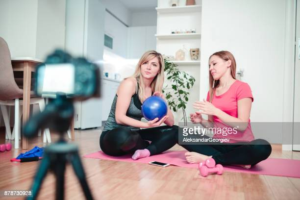 two cute females making vlog about pilates and healthy lifestyle - aleksandar georgiev stock photos and pictures