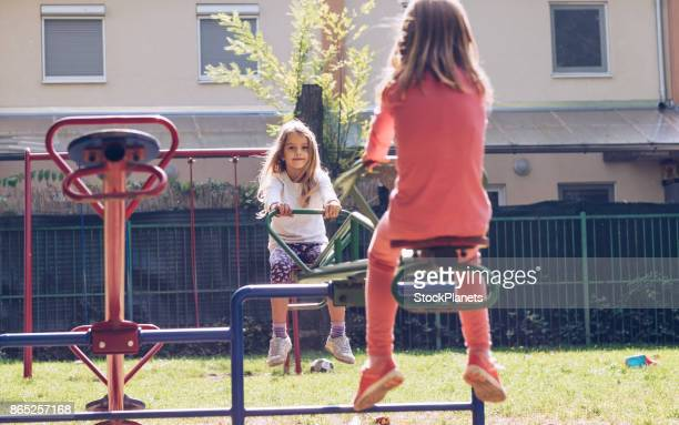Two cute girls on seesaw
