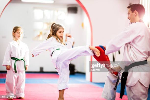 two cute girls on taekwondo training, kicking and learning self-defence - taekwondo kids stock photos and pictures