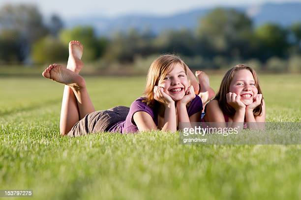 two cute girls posing in a field - little girls bare feet stock photos and pictures