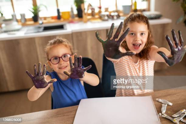 two cute girls showing their hands while finger painting at home - 4 girls finger painting stock pictures, royalty-free photos & images