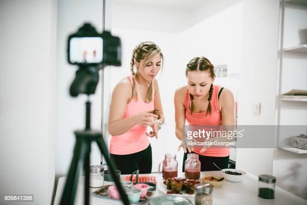 2 つのかわいい女の子のスムージーのフルーツを試みることと健康食品についてビデオブログを作る