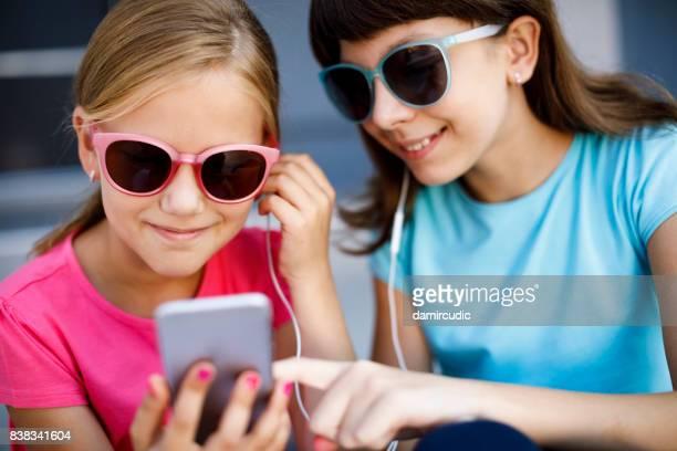 twee leuke meisjes gebruiken slimme telefoon en luisteren muziek - 10 11 jaar stockfoto's en -beelden
