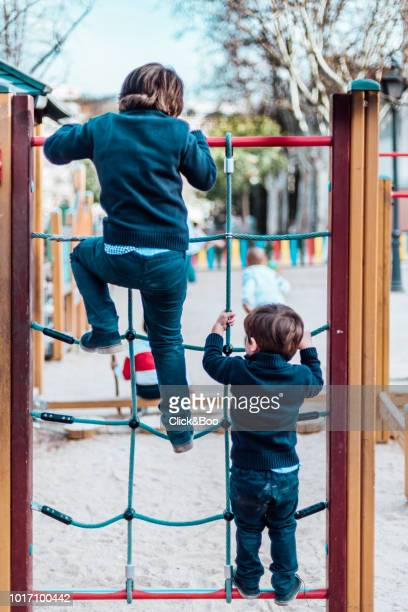 Two cute little boyc playing outdoors in a park