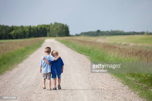 Two Cute Preschool Boys Walking Down the Road