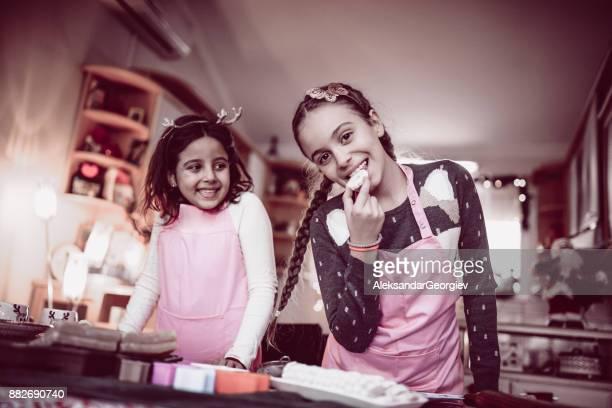 Deux sœurs mignonnes mangeant leurs Cookies après cuisson classe