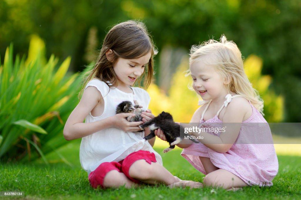 e81bef8a2f52a Zwei Süße Schwestern Spielen Mit Kleinen Kätzchen Stock-Foto - Getty ...
