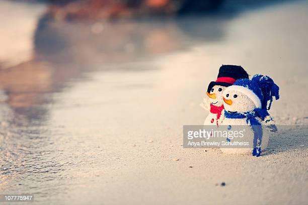 Two cute snowmen on the beach in the Caribbean