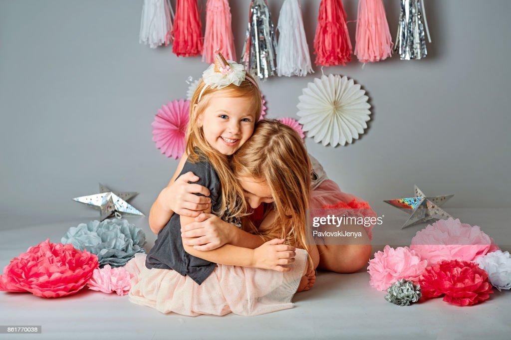 aaff5cb84b61b Zwei süße junge Schwestern posieren zusammen in einem Studio. Vertikal  gerahmte Schuss isoliert gegen eine graue Studio-Hintergrund. Die ältere  Schwester ...