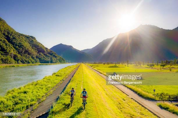 two cyclist ride e-bike on the riverside of adda river. - italia stock-fotos und bilder