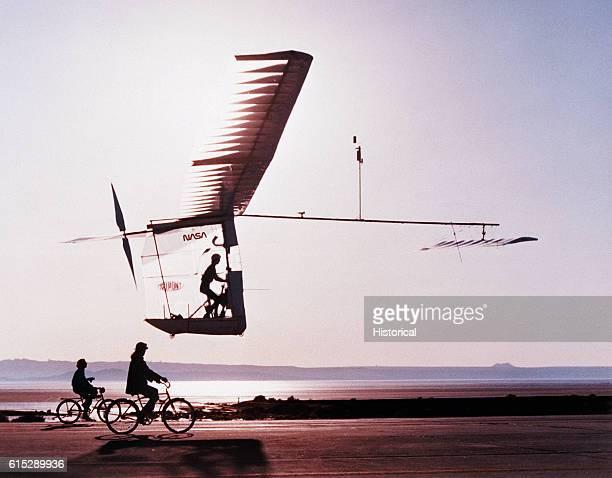 Two cyclists follow a an experimental craft called the Gossamer Albatross a aerodynamic lightweight plane that a pilot propels by pedaling