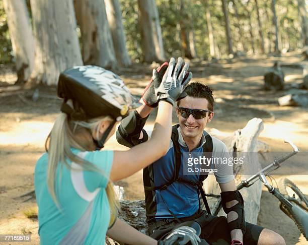 Dos ciclistas fiving Sí, alta