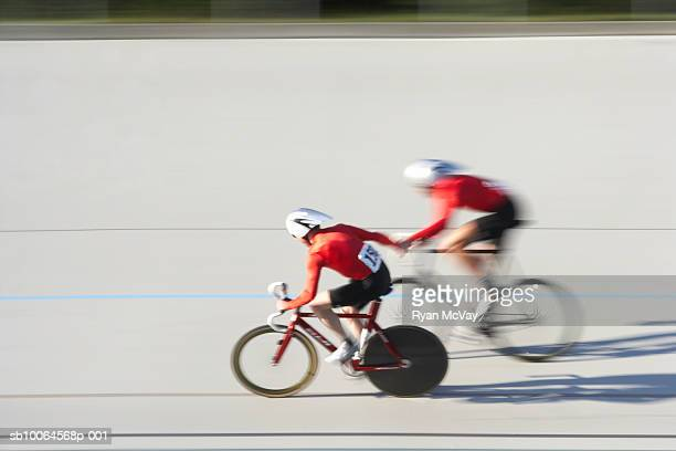 two cyclists in action on velodrome track - cycle vehicle stock photos and pictures