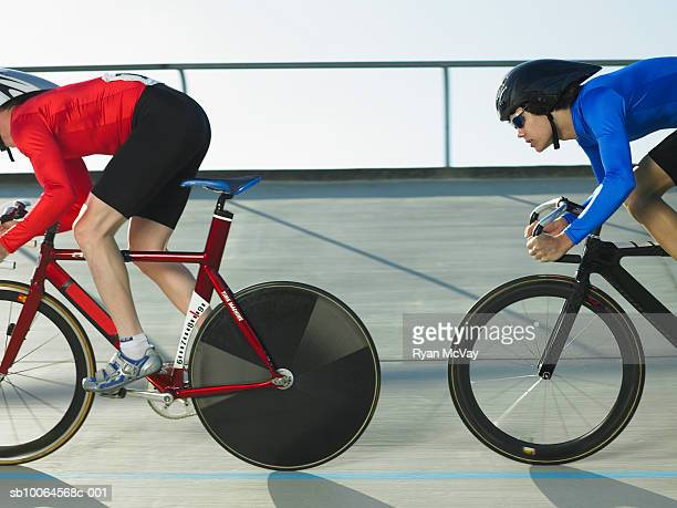 Two cyclists in action on velodrome track, side view