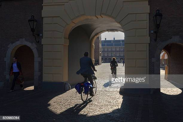 two cyclists on binnenhof in the hague - binnenhof stock photos and pictures
