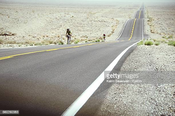 two cyclists on desert road - eternity stock pictures, royalty-free photos & images