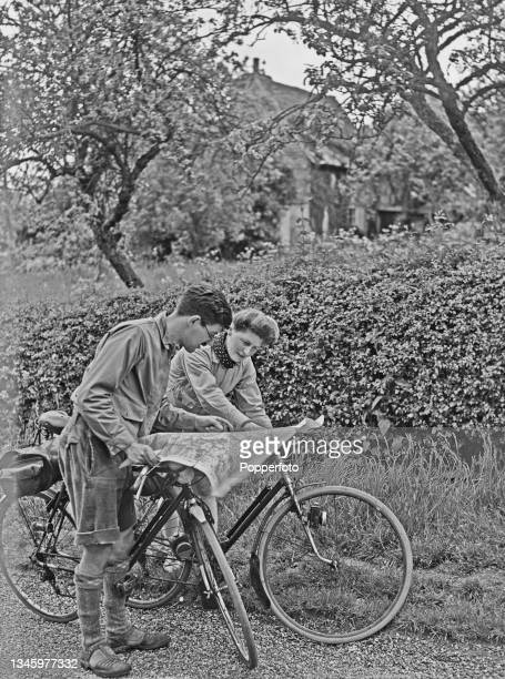 Two cyclists, one male and one female, study a map of their route as they prepare to set off on a cycle ride from their overnight stay at Ewhurst...