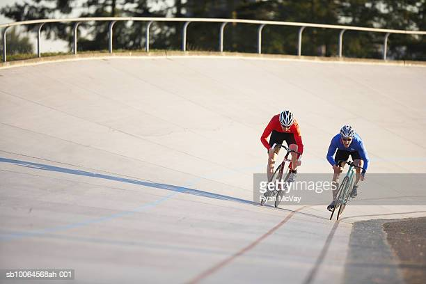 Two cyclists racing on velodrome