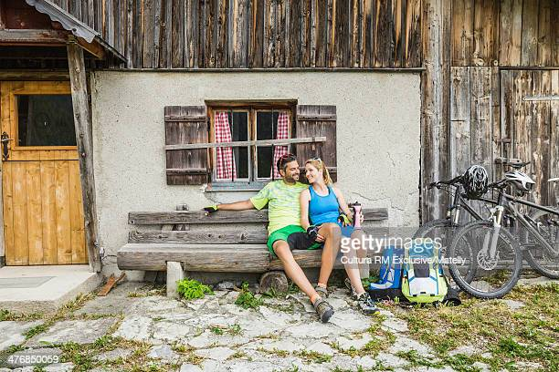 Two cyclists sitting on bench outside chalet, Tyrol, Austria