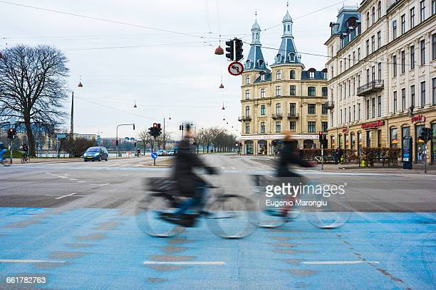 two cyclists speeding along blue city cycle path, copenhagen, denmark - danish culture stock pictures, royalty-free photos & images