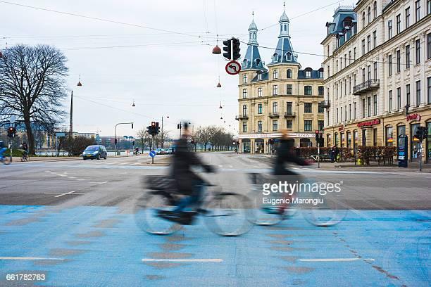 Two cyclists speeding along blue city cycle path, Copenhagen, Denmark