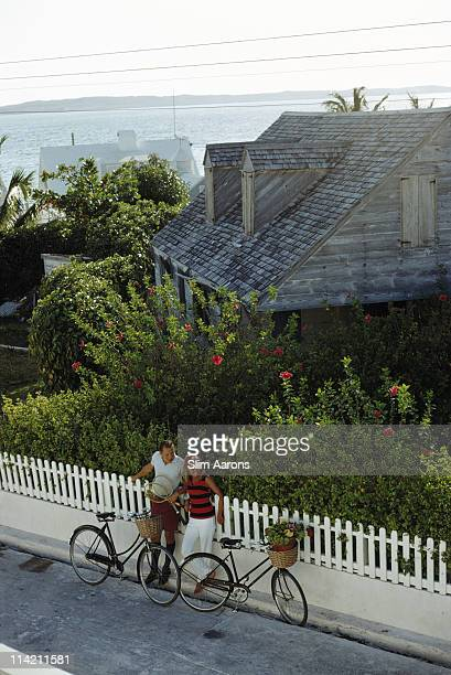 Two cyclists stop for a break at Dunmore Town on Harbour Island in the Bahamas, circa 1965. One of the cyclists, a man, holds two tennis raquets,...