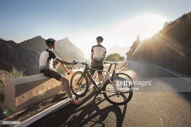 two cyclists watching at sunset in mountains - sports jersey stock pictures, royalty-free photos & images
