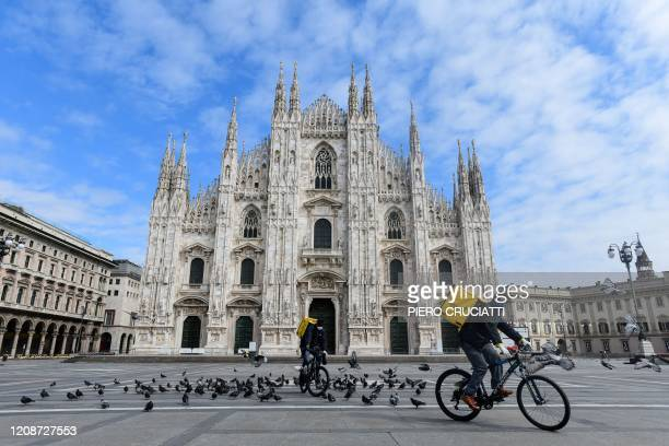 Two cyclists working for the food delivery service Glovo ride their bike across a deserted Piazza Duomo in Milan, on March 31 during the country's...