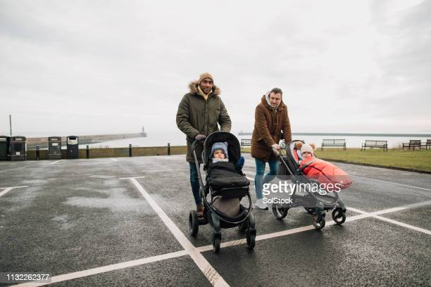 two dads and their baby sons - paternity leave stock pictures, royalty-free photos & images